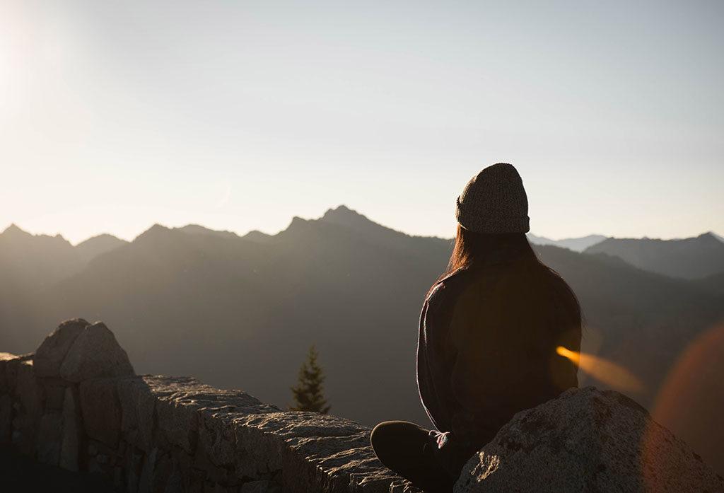 personne qui fait de la sophrologie face à une montagne